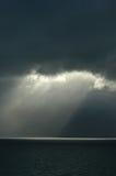 Rupturas da luz solar através das nuvens pretas Fotos de Stock Royalty Free