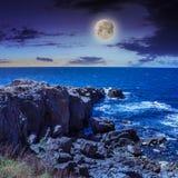 Rupturas da onda do mar sobre pedregulhos na noite Imagem de Stock Royalty Free