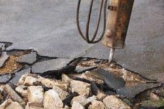Rupture de la surface de la route pour la réparation avec le marteau piqueur Photo libre de droits