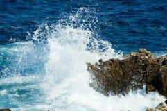 Ruptures d'onde sur les roches Photographie stock