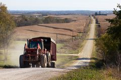 Rural agricultural landscape of U.S. Midwest. Foreground: tractor pulling a trailer; background: corn field and hilly gravel road Royalty Free Stock Photos