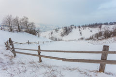 Rural alpine winter landscape with fence and path Stock Photos