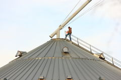 Rural American Man On Top Of Metal Grain Bin Stock Photo