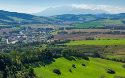 Rural area around the town. Grassy hill and agricultural fields. High tatra mountain ridge in the distance. view from the top of a castle tower Royalty Free Stock Photo