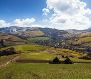 Rural area in Carpathian mountains. Haystacks on grassy agricultural fields. village down in the valley. mountain with snowy top on a beautiful springtime day royalty free stock photos