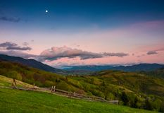 Rural area at dusk with moon on cloudy sky. Beautiful mountainous landscape with agricultural fields and wooden fences on grassy slopes in springtime Royalty Free Stock Photo