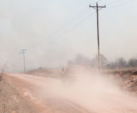 Rural area firetruck on its way to stop a wildfire. The smoke of which is covering the sky obstructing visibility Royalty Free Stock Image