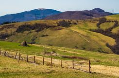 Rural area on rolling hills in springtime. Wooden fence and haystack near the road. lots of electric poles Stock Photos