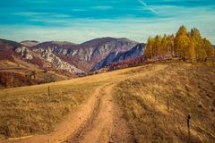 Rural autumn landscape with a dirt road. In the mountains Royalty Free Stock Photo