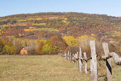 Rural autumn landscape in the mountains . The fence passing into distance tiny house Royalty Free Stock Photos