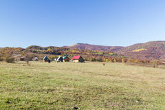 Rural autumn landscape in the mountains . Small houses and horses Stock Photos