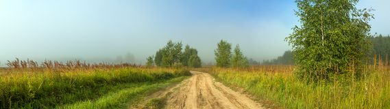 Rural autumn landscape panorama with the road, fog,field, trees. And birches. panoramic view Royalty Free Stock Image
