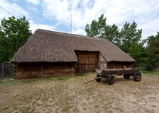 Rural barn. Barn covered with straw and horse-drawn carriage. Exhibits from the museum in the Polish countryside in Maurzyce in the region Łowicz Stock Photos