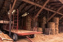 Hay bales and a trailer in a barn Royalty Free Stock Photography