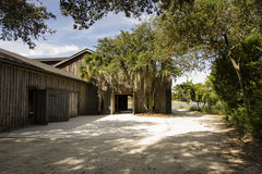 Rural Barn and Warehouse Near Water. A view of a rural barn or storage warehouse located near a waterway in a southern location where you can see Spanish moss in Stock Photo