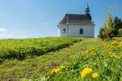 Rural baroque chapel on flowering meadow Stock Image