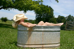 Rural bath. Young woman bathing country or rural style in a galvanized horse trough royalty free stock photos