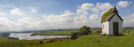 Rural bavarian panorama with little chapel and lake view Royalty Free Stock Images