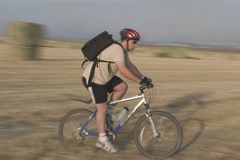 Rural Bike riding. A bike rider in a middle of a cropped field Stock Image