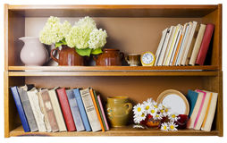 Rural bookshelf. Rural village bookshelf with old broken books, ceramic pots, clocks and daisies flowers. . Fromt view royalty free stock images