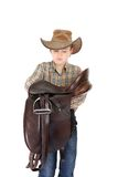 Rural boy holding a saddle Stock Photos