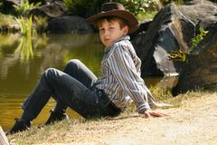 Rural boy sitting by riverbank Stock Images