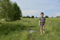 Rural boy stands barefoot on the road in the field. Royalty Free Stock Image