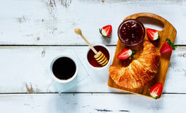 Rural breakfast with croissant. Top view of rural breakfast with cup of coffee, croissant, jam, honey and strawberries on rustic white wooden table. Background Stock Photo