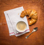 Rural  breakfast with cup of coffee and croissants on wooden background Stock Image