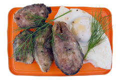 Rural breakfast- fried salmon with fried eggs and parsley Royalty Free Stock Images
