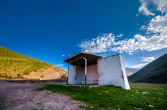 Rural bus stop of stone at the mountain road. Empty transport station. Abandoned building Royalty Free Stock Photography
