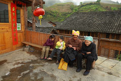 Rural China, Asian grandmother with grandchildren, sit on bench. Stock Images