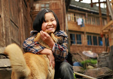The rural Chinese teenage girl plays with the ginger dog, near a Royalty Free Stock Photos
