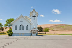 Rural Church. A small white church with a black cross, a cracked parking lot, and small trees sits on the prairie of Eastern Washington Royalty Free Stock Photography