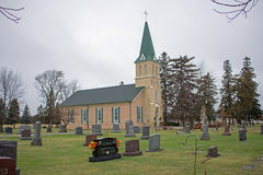 A Rural Church Cemetery. The church has a new green metal roof. The steeple has a cross on the top of it. Trees surround the site Stock Images