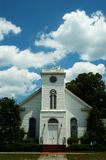 Rural Church and Clouds. Rural white wooden church with clouds in the sky - vertical image Stock Image
