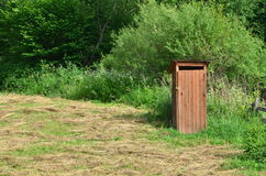 Rural toilet. Vintage wooden closet outdoor in rural area royalty free stock photo