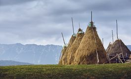 Rural cloudy landscape with haystacks in Transylvania, Romania Stock Photo