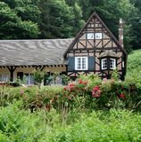 Rural Cottage. In Normandy, France with Flower covered Hedgerow to the front Royalty Free Stock Photo