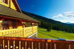 Rural cottage in the mountains and green meadow. Sunset scenery. Slovakia. Royalty Free Stock Images
