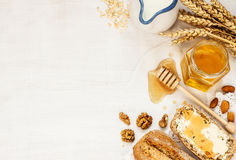 Rural or country breakfast - bread rolls, honey jar and milk. Rural or country breakfast - bread rolls, honey jar, milk, nuts and wheat on white wood from above stock photography