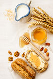 Rural or country breakfast - bread rolls, honey jar and milk. Rural or country breakfast - bread rolls, honey jar, milk, nuts and wheat on white wood from above royalty free stock photography