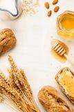 Rural or country breakfast - bread rolls, honey jar and milk. Stock Photos