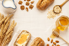 Rural or country breakfast - bread rolls, honey jar, milk. Stock Photo
