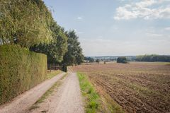 Rural Country Road. A rural country road leads through recently harvested farmland toward a distant village in Belgium in early fall royalty free stock photography
