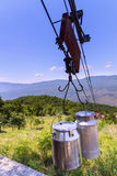 Rural country scene in mountains: metal milk churns hanging on a Stock Photography
