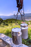 Rural country scene in mountains: metal milk churns hanging on a Royalty Free Stock Image