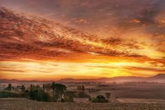 Rural countryside at sunrise. Rural landscape of misty fields in autumn colors at sunrise Royalty Free Stock Photos