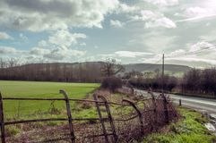 Craggy old railings in the British countryside. A rural countryside lane with clouds and blue skies and crops in the English countryside royalty free stock photo