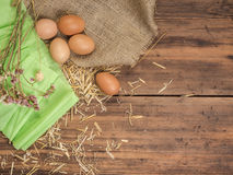 Rural creative background with brown eggs, burlap, straw, green paper and dry flowers on wooden table from old planks Stock Photography